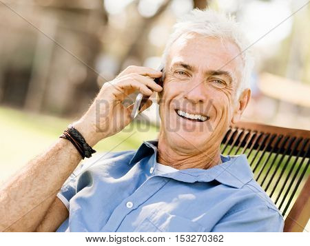 LoMature man outdoors using mobile phone