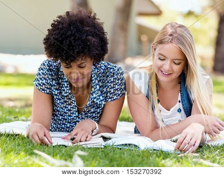 Two girls are resting in park with books