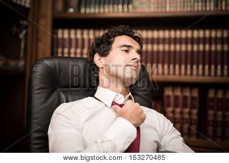 Businessman relaxing and loosening his necktie