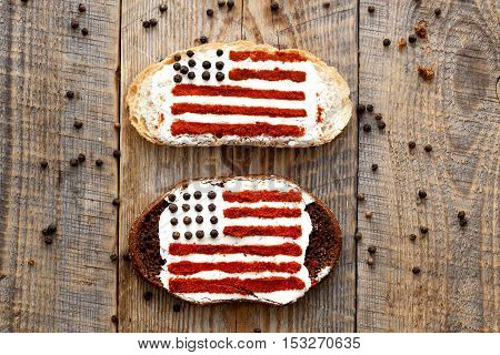 Two sandwiches with image of american flag on wooden table, top view.