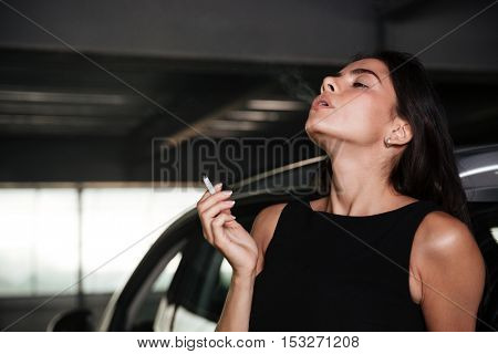 Attractive young woman standing and smoking on car parking