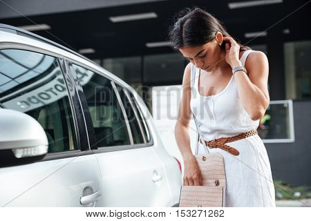 Pretty young woman standing and looking keys of car in her bag outdoors