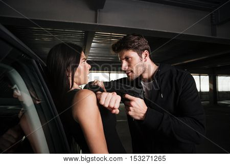Criminal man standing and threatening to frightened young woman near the car