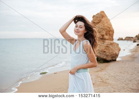 Happy attractive young woman in white dress standing on the beach