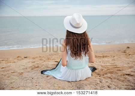 Back view of young woman with long hair in hat and dress sitting on the beach