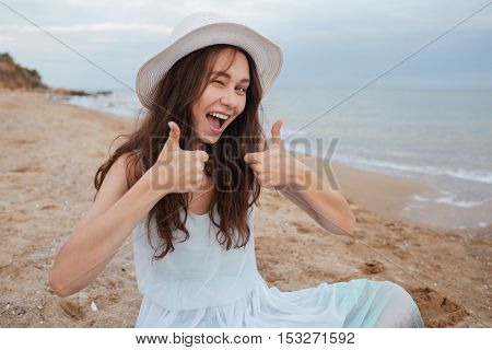 Cheerful playful young woman winking and showing thumbs up on the beach