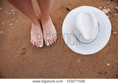 Top view of barefoot woman legs and hat on the beach