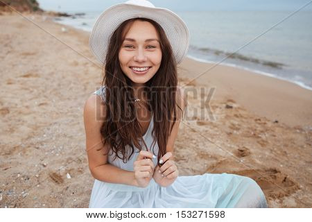 Smiling cute young woman in white dress and hat sitting on the beach