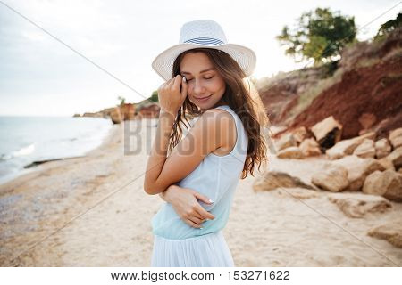 Sensual pretty young woman in white hat on the beach