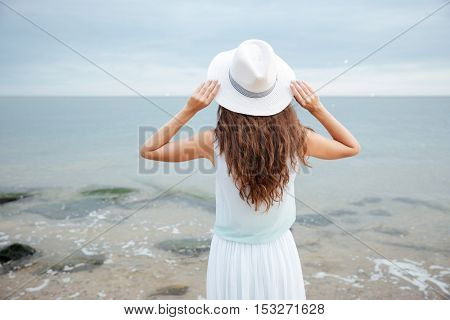 Back view of woman in white hat standing and looking at the sea