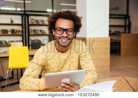 Portrait of smiling confident african young man using tablet in library