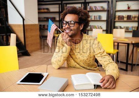Happy african american young man in glasses with US flag, books and tablet sitting in library