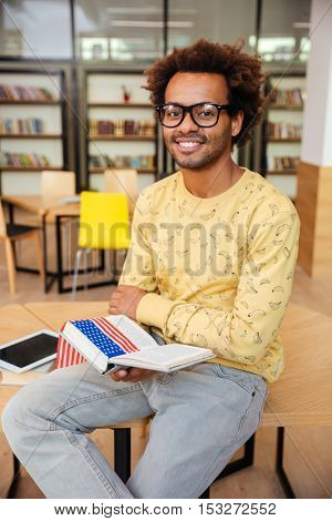 Happy african american young man in glasses sitting and reading book in library