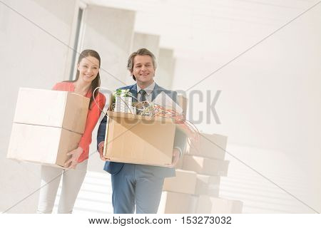 Smiling businessman and businesswoman carrying cardboard boxes in new office