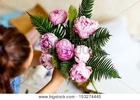 Florist making a bouguet of pink peonies in workshop