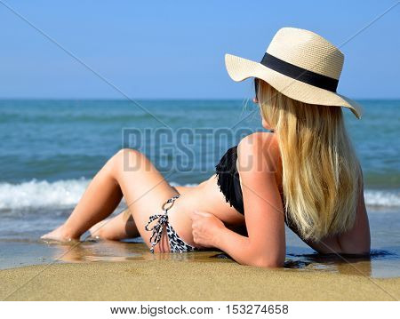 Caucasian girl with hat on the beach. Summer vacation by the sea.
