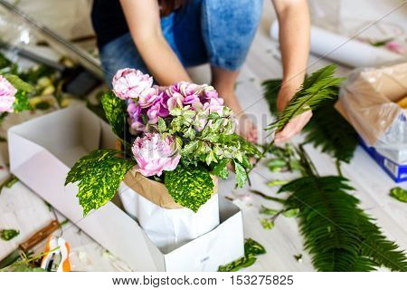Florist making a bouguet of white flowers and peonies in workshop