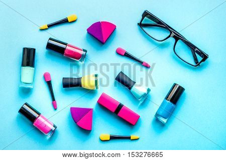 concept cosmetic set with glasses on blue background top view.
