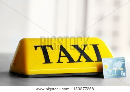 Yellow taxi roof sign with credit card on gray table, closeup