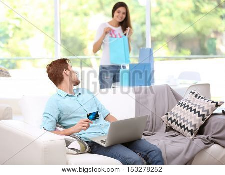 Young man with laptop shopping online and woman on background