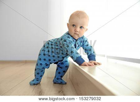 Adorable little baby standing beside wooden windowsill