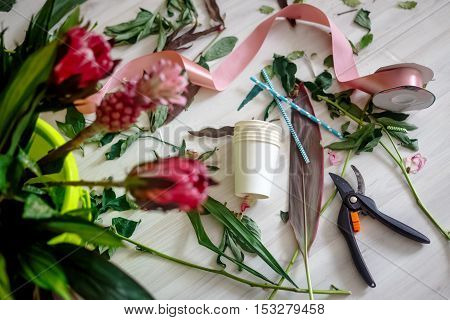 Red flowers with scissors in workshop place before making bouquet