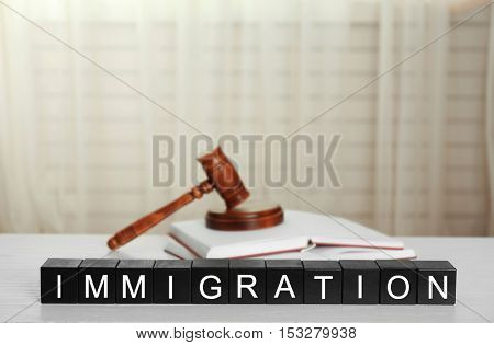 Black cubes with word IMMIGRATION and gavel on white table