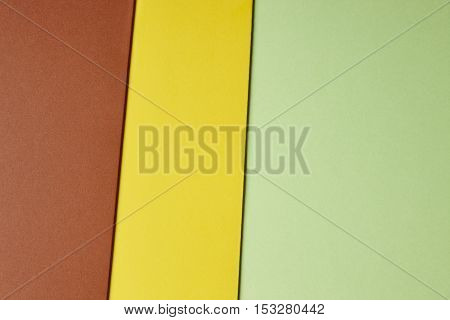 Colored cardboards background in brown yellow green tone. Copy space. Horizontal