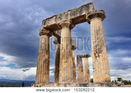 Colonnade of the Temple of Apollo under dramatic cloudy sky at sunset in Ancient Corinth. Greece