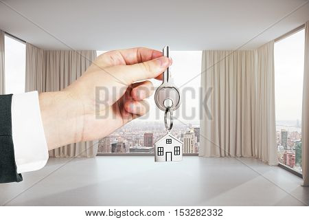 Close up of hand holding key with house chain in modern interior with city view. Real estate concept