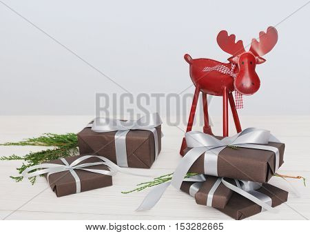 Lots of gift boxes and fir tree branches with decorative red deer or elk on white wood background. Presents in dark paper decorated with satin ribbon bows. Christmas and winter holidays concept.