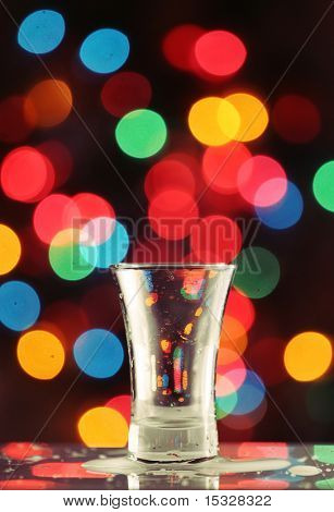 Empty shot glass with liquid drops on a fairy light background, please check for more