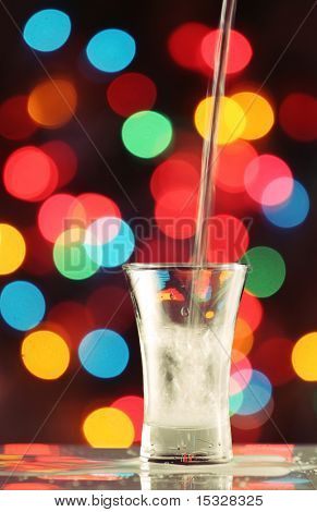 Pouring a seethrough liquid in to a shot glass, fairy light background, please check for more