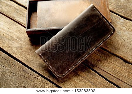 Brown leather purse on wooden background