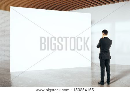 Thoughtful businessman in suit looking at blank billboard in white birck interior. Mock up 3D Rendering
