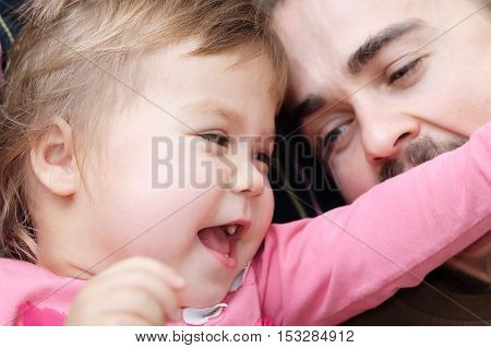 cheerful little girl and daddy having fun laughting very emotional