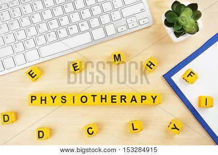 Workplace with keyboard and word PHYSIOTHERAPY made of yellow blocks on wooden background