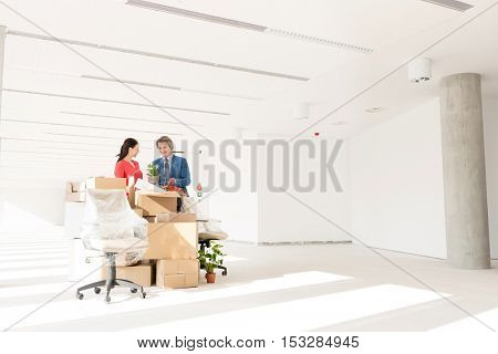 Business people discussing while standing by cardboard boxes in new office