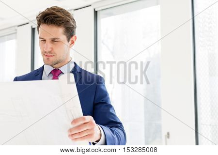 Confident young businessman reading blueprint in new office