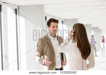 Young businessman talking with female colleague in new office