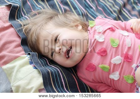 cheerful cute child happy laughing lying on bed