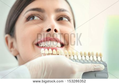 Dentist matching teeth colour in office