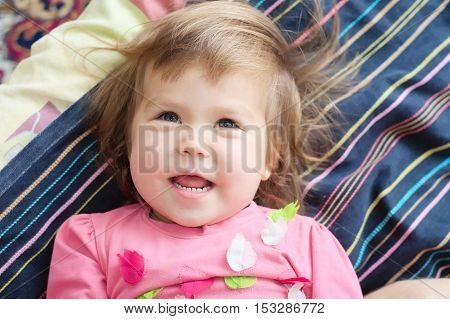 cheerful cute kid happy smiling lying on bed