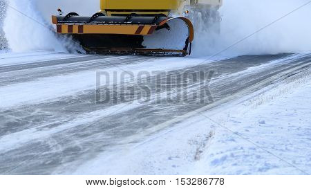 Snowplow removes snow off icy road in winter.