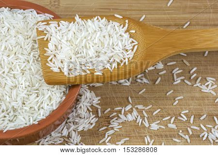 White basmati rice on vane and in the clay bowl on the light wooden background