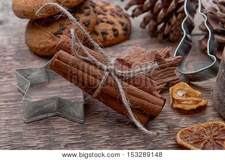 Composition of cinnamon sticks, cookie cutter and natural decor on wooden background, close up view