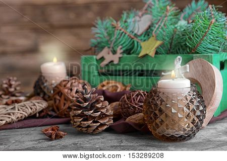 Composition of candle and natural decor on wooden background, close up view