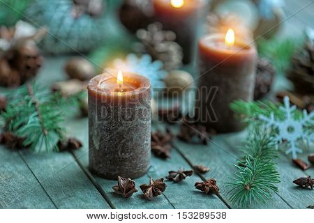 Candle, anise stars and fir tree branch on wooden background, close up view