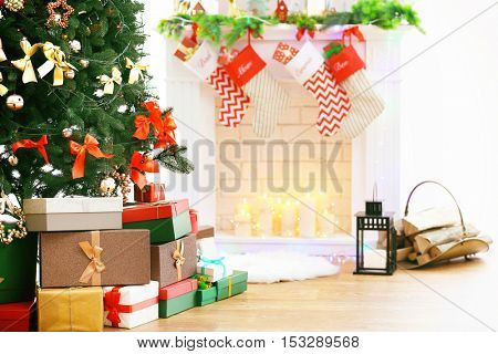 Beautiful Christmas tree and boxes with presents near fireplace