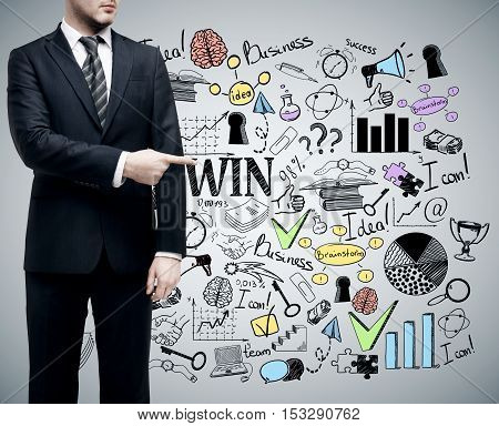 Businessman pointing at creative business sketch on grey background. Success concept